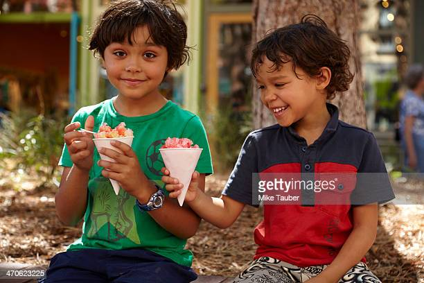Mixed race boys eating ice cream outdoors