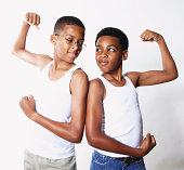 Mixed race boys flexing their muscles