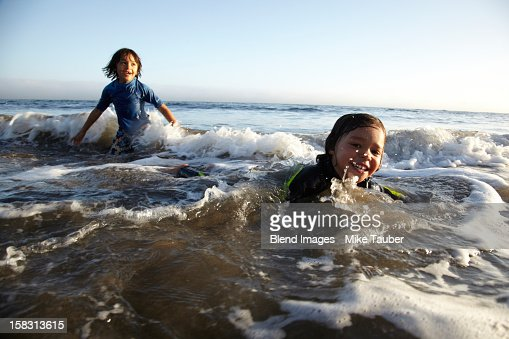 mixed race boys swimming in ocean stock photo getty images