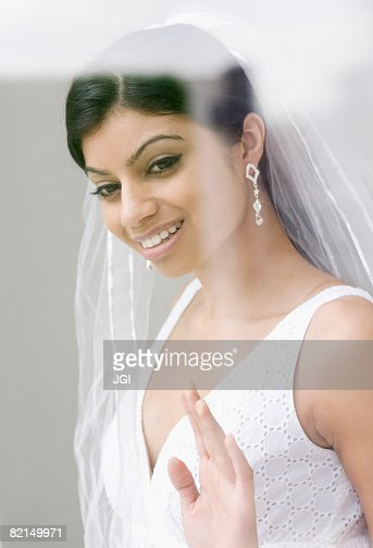 Mixed Race bride looking out window  : Stock Photo