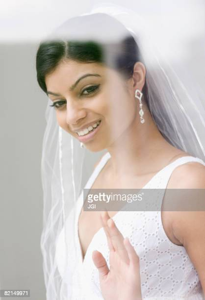 Mixed Race bride looking out window