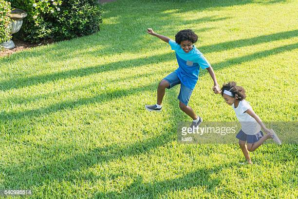 Mixed race brother and sister playing in park