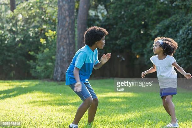 Gemischtes Bruder und Schwester Spielen im park