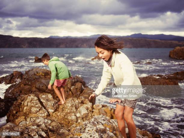 Mixed race brother and sister playing on rocky beach