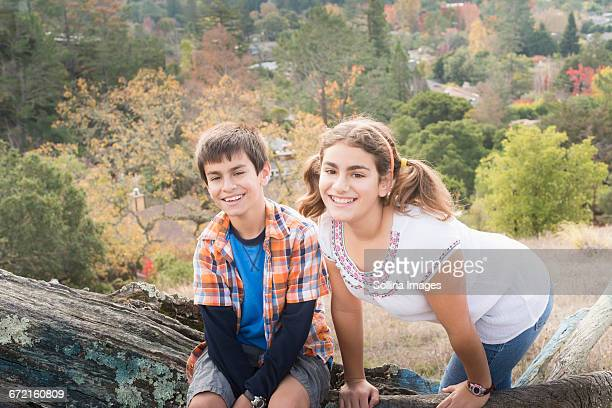 Mixed Race brother and sister posing on log