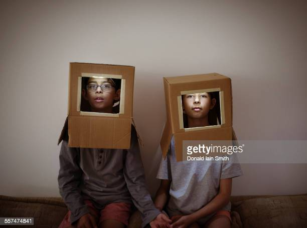 Mixed race brother and sister wearing cardboard box astronaut helmets