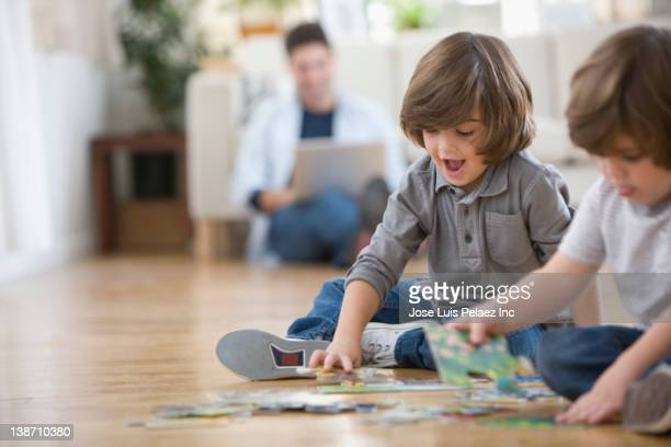 Mixed race brothers putting together puzzle on floor