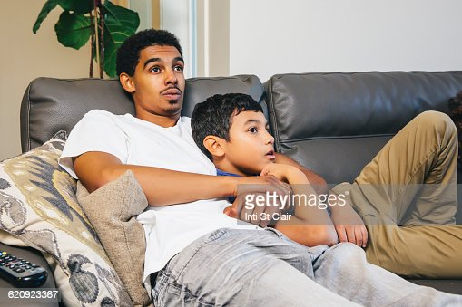 Mixed race brothers watching television on sofa : Stock Photo