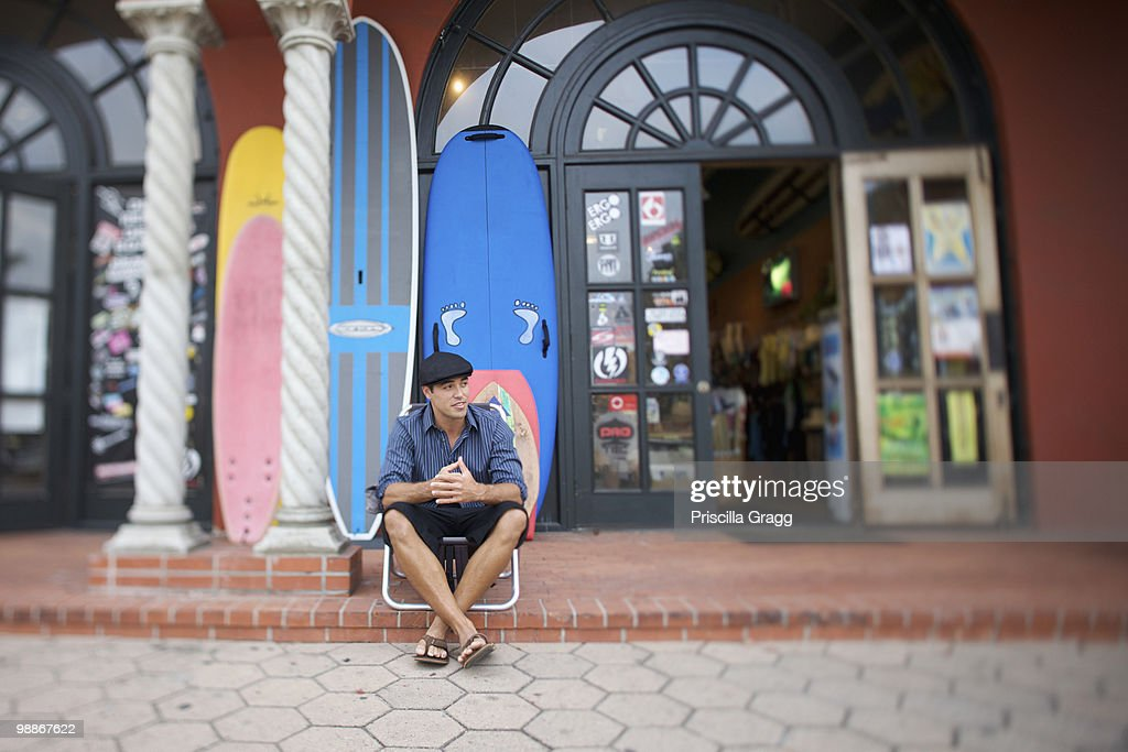 Mixed race business owner sitting outside store