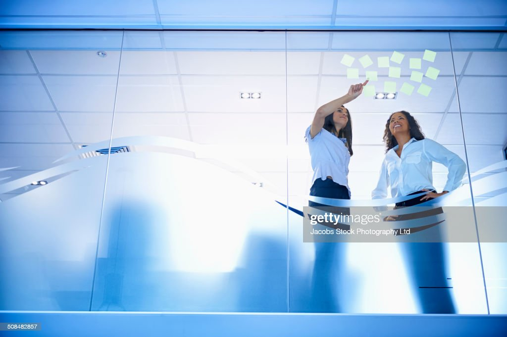 Mixed race business women reading adhesive notes in office