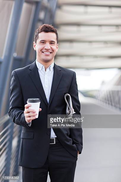 Mixed race businessman carrying coffee and newspaper