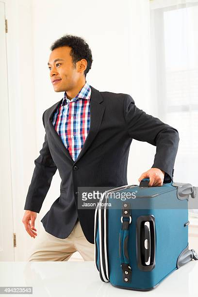 Mixed race businessman carrying suitcase