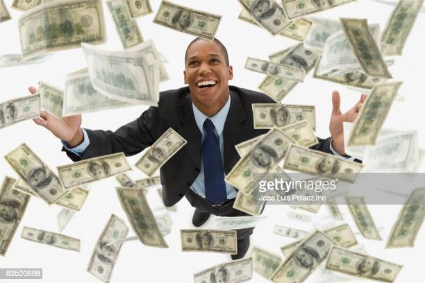 Mixed race businessman catching falling 100 dollar bills