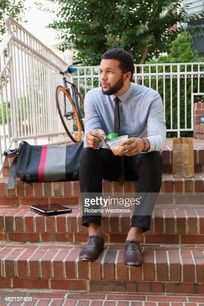Mixed race businessman eating on front stoop
