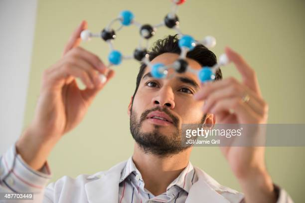 Mixed race businessman examining molecular model