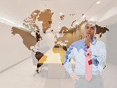 Mixed race businessman examining world map