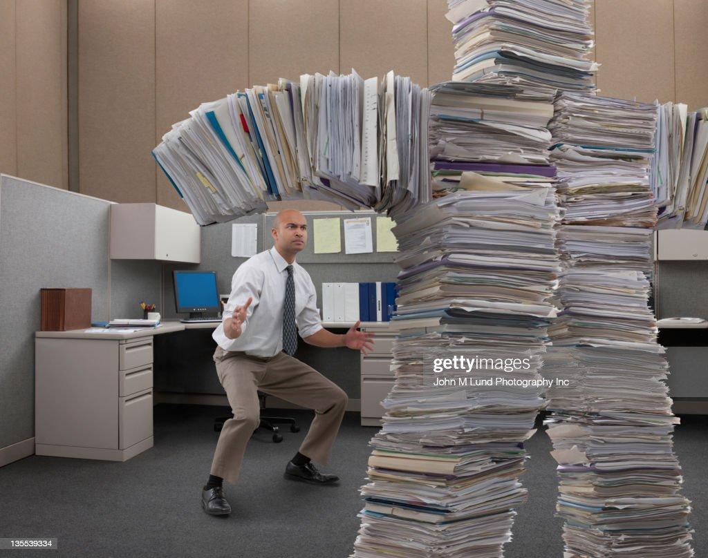 Mixed race businessman facing paperwork monster : Stock Photo