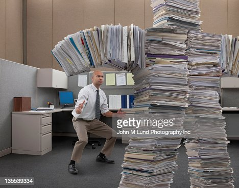 Mixed race businessman facing paperwork monster : Stock Photo