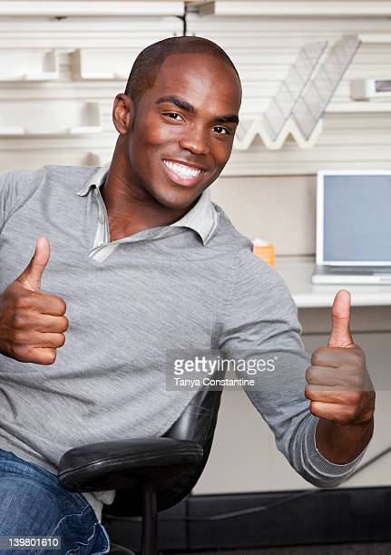 Mixed race businessman giving thumbs up in office