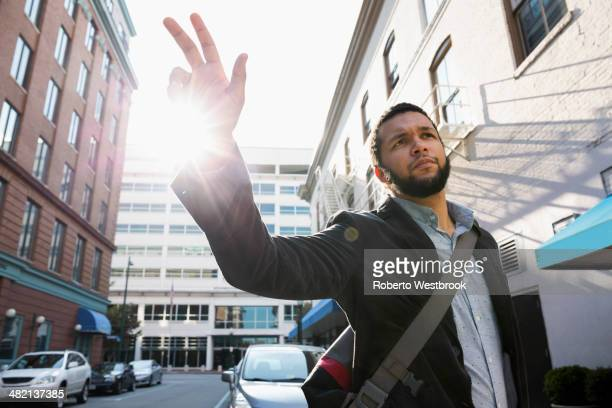 Mixed race businessman hailing taxi on city street