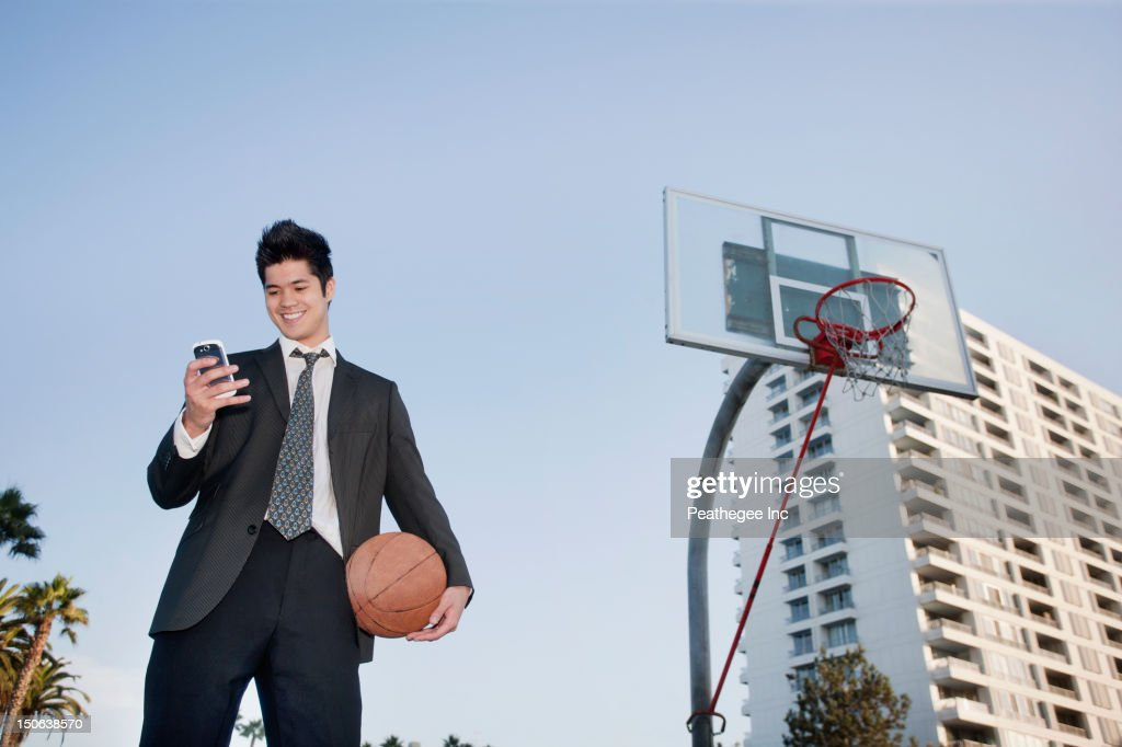 Mixed race businessman holding basketball and text messaging on cell phone : Stock Photo