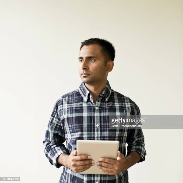 Mixed race businessman holding digital tablet