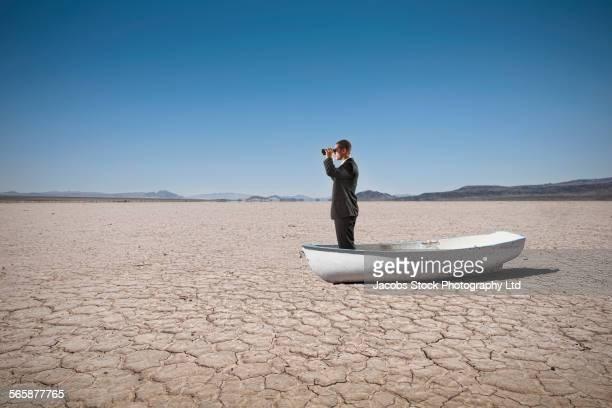 Mixed race businessman in boat in dry desert landscape