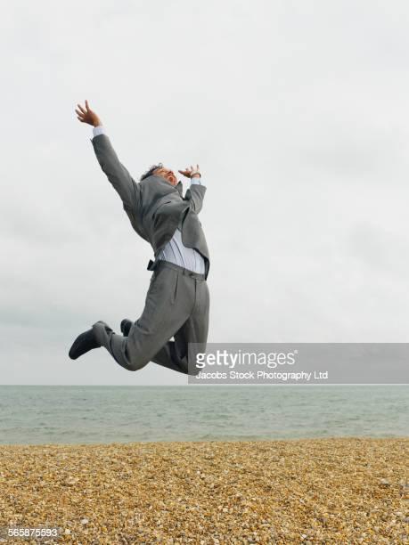 Mixed race businessman jumping for joy on beach