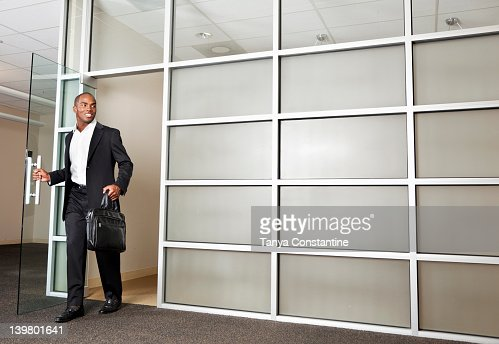 Mixed race businessman leaving modern office : Foto de stock