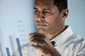 Mixed race businessman looking at bar graph
