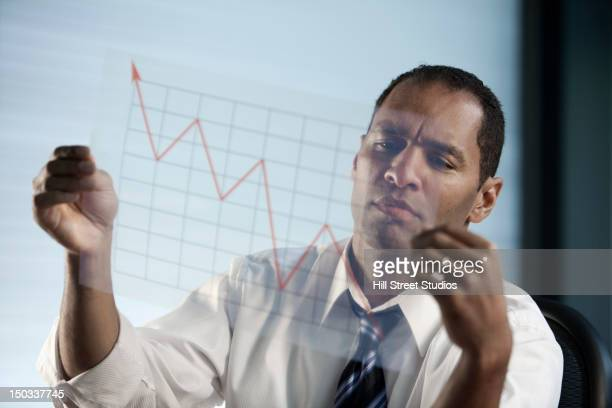 Mixed race businessman looking at line graph
