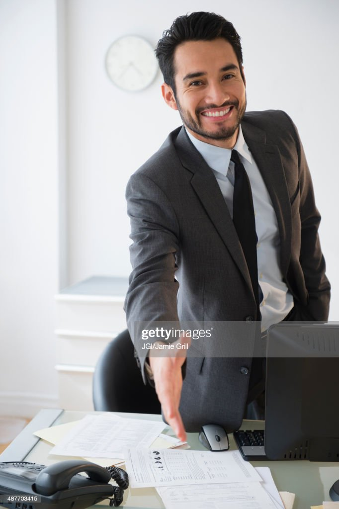 Mixed race businessman offering handshake in office