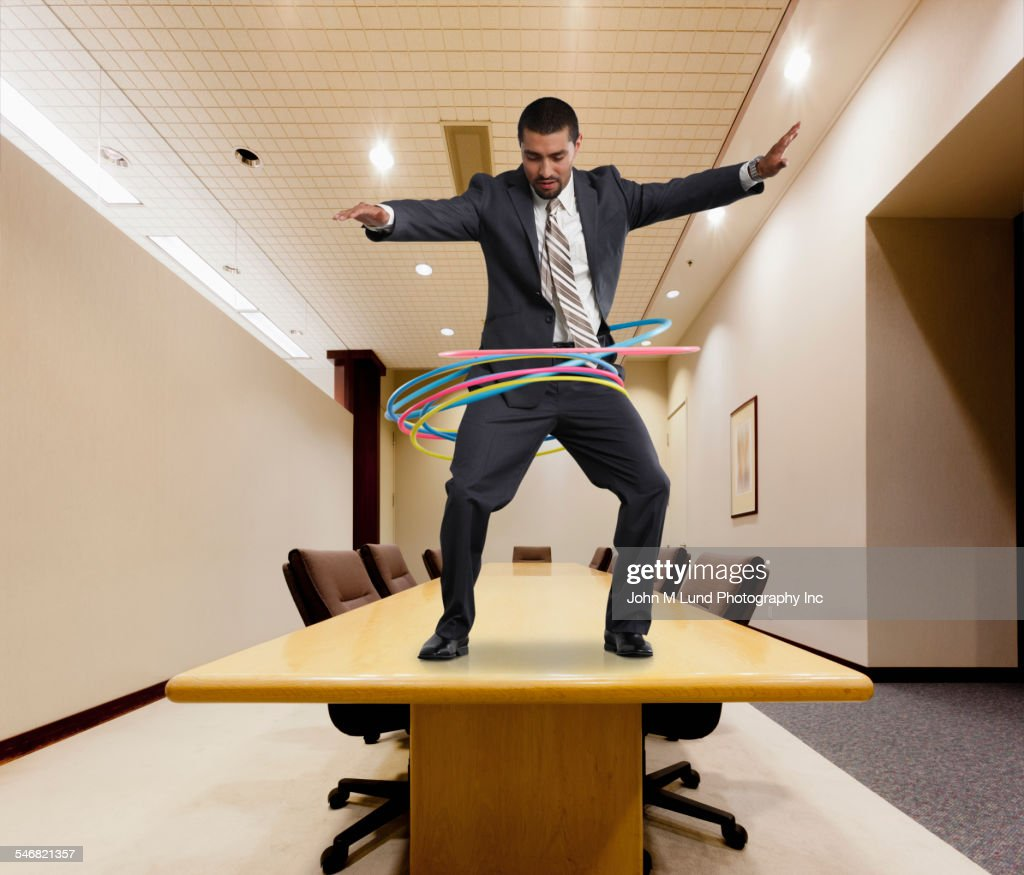 Mixed race businessman on conference table spinning plastic hoops