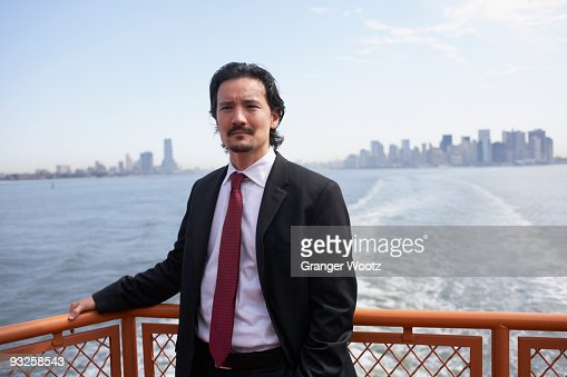 Mixed race businessman on ferry : Stock Photo