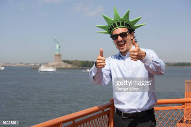 Mixed race businessman on ferry wearing Statue of Liberty hat