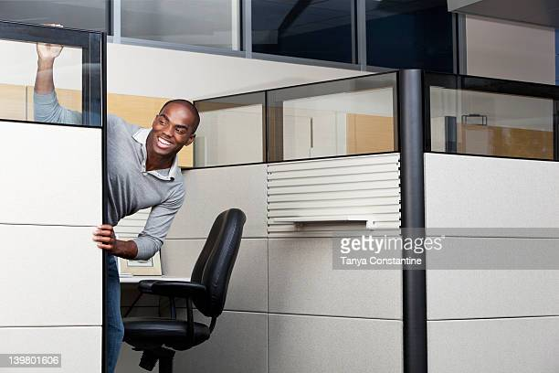 Mixed race businessman peering out from office cubicle