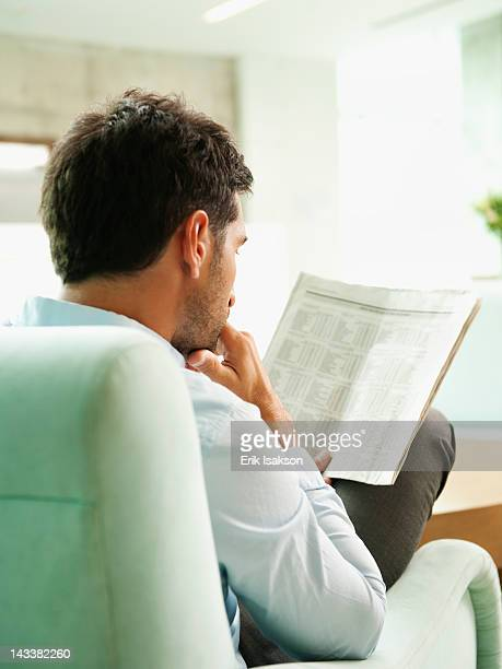Mixed race businessman reading newspaper