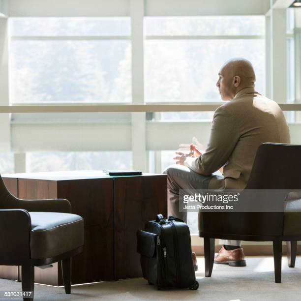 Mixed race businessman relaxing in office