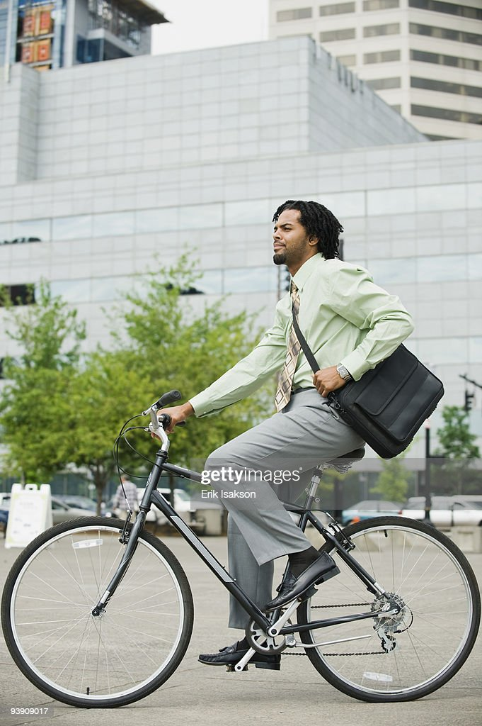 Mixed race businessman riding bicycle in city : Stock Photo