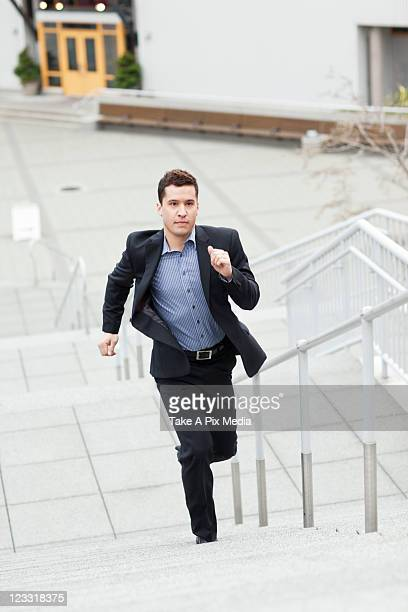 Mixed race businessman running up stairs