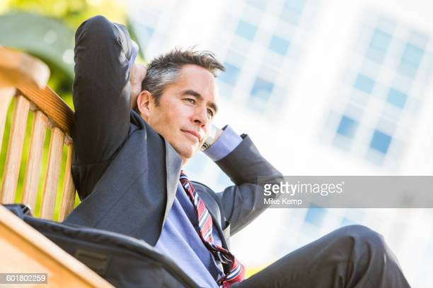 Mixed race businessman sitting outdoors