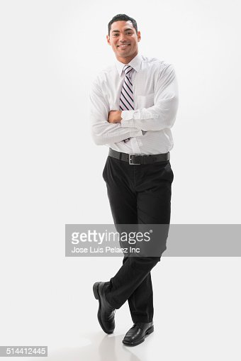 Mixed race businessman smiling with arms crossed