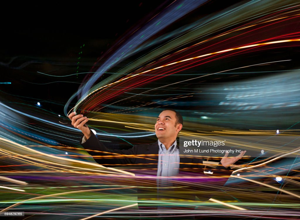 Mixed race businessman standing in blurred lights