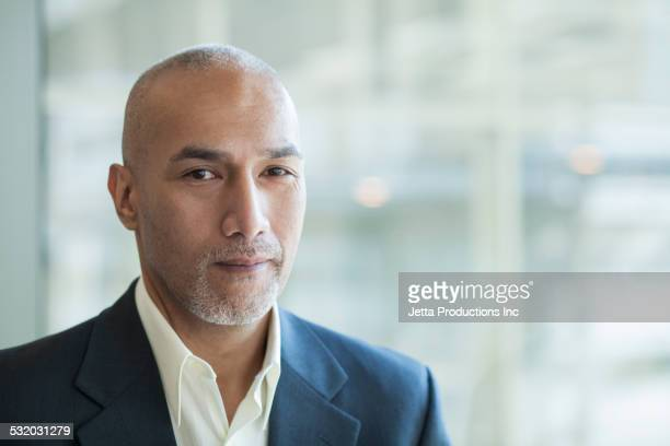 Mixed race businessman standing in office