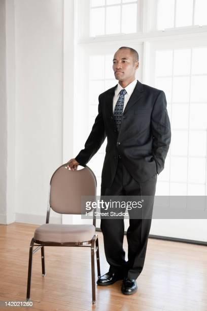 Mixed race businessman standing near chair
