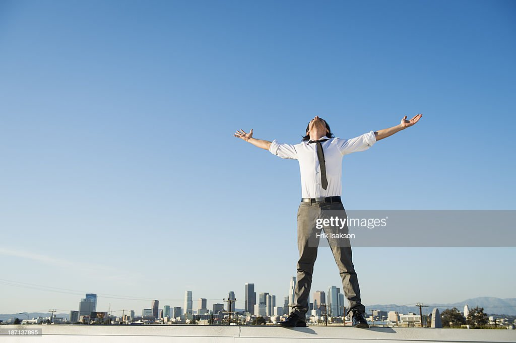 Mixed race businessman standing on urban rooftop : Stock Photo