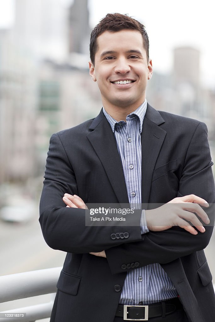 Mixed race businessman standing outdoors : Stock Photo