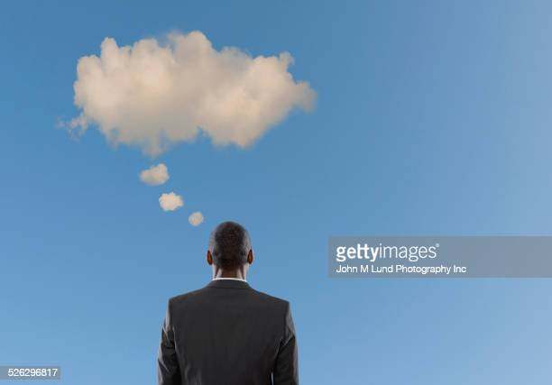 Mixed race businessman standing under thought bubble cloud