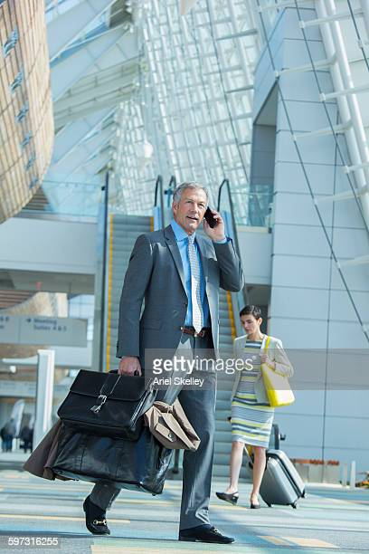 Mixed race businessman talking on cell phone in airport