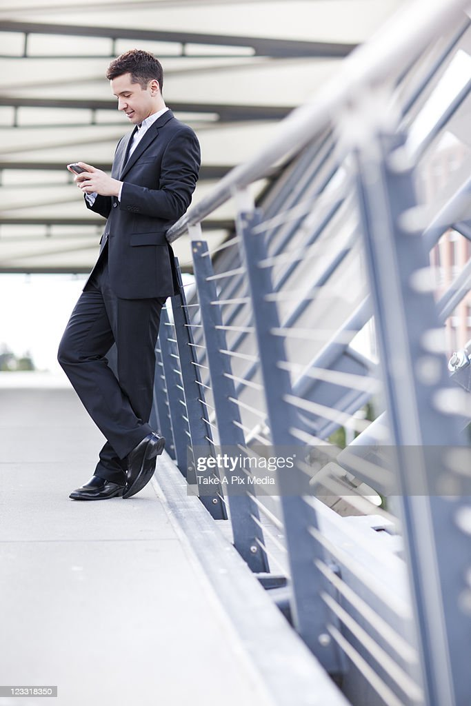 Mixed race businessman text messaging on cell phone : Stock Photo